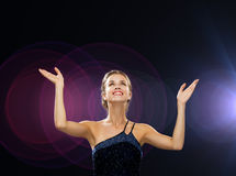 Smiling woman raising hands and looking up Royalty Free Stock Images