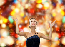 Smiling woman raising hands and looking up Stock Images