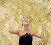 Smiling woman raising hands and looking up Royalty Free Stock Photography