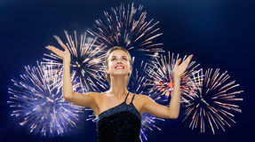 Smiling woman raising hands up over firework Stock Photo