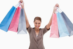Smiling woman raising her shopping bags Stock Photos