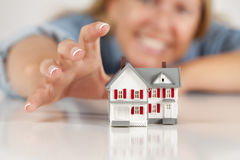 Smiling Woman Reaching for Model House on White Stock Photography