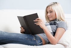 Smiling Woman Reading Book on Couch Stock Image
