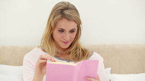 Smiling woman reading a book in her bed stock video footage