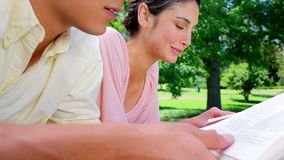 Smiling woman reading a book with her boyfriend stock footage