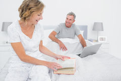 Smiling woman reading book while husband is using laptop Stock Images