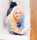 Smiling woman reading book and lying on couch Royalty Free Stock Image