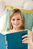 Smiling woman reading a book lying on a sofa Royalty Free Stock Photo