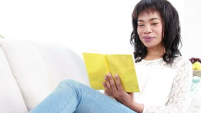 Smiling woman reading a book stock video