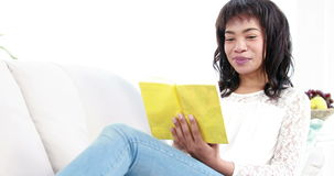 Smiling woman reading a book stock video footage
