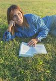 Smiling woman reading a book in nature royalty free stock photography