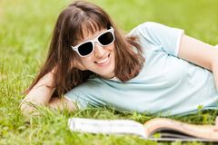 Smiling woman reading book outdoor Royalty Free Stock Photo