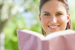 Smiling woman reading a book in the park Stock Photography