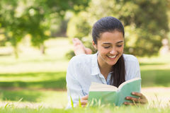 Smiling woman reading a book in park Royalty Free Stock Photos