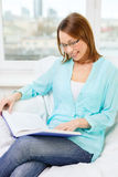 Smiling woman reading book and sitting on couch Royalty Free Stock Image