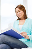Smiling woman reading book and sitting on couch Stock Images