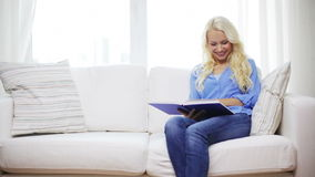 Smiling woman reading book and sitting on couch stock video
