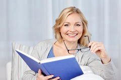 Smiling woman reading book and sitting on couch Stock Photography