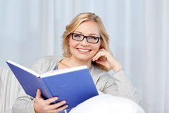 Smiling woman reading book and sitting on couch Stock Image