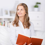 Smiling Woman Reading Book On Sofa Stock Photography