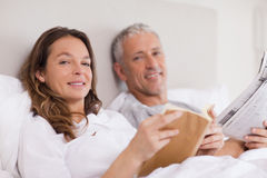 Smiling woman reading a book whith her husband Stock Image