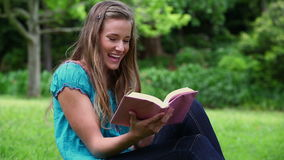 Smiling woman reading a fascinating novel. In a park stock footage