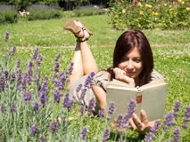 Smiling woman reading in lavender fields. Young red woman reading a book lying on the grass Stock Images