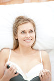 Smiling woman reading lying on her bed Stock Images