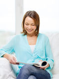 Smiling woman reading magazine at home Stock Photography