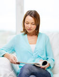 Smiling woman reading magazine at home Stock Photos