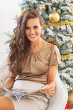 Smiling woman reading magazine near christmas tree Royalty Free Stock Photo