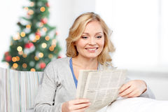 Smiling woman reading newspaper at christmas stock photos