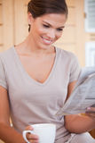 Smiling woman reading newspaper while having coffee Stock Photography