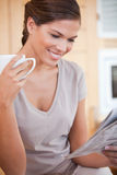 Smiling woman reading newspaper while having tea Stock Photography