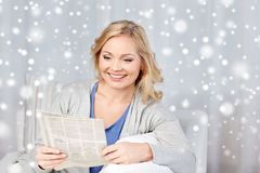 Smiling woman reading newspaper at home Royalty Free Stock Images