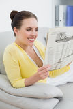 Smiling woman reading newspaper on sofa at home Royalty Free Stock Photos