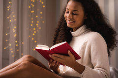 Smiling woman reading novel Stock Images