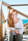 Smiling woman reading at the seaside Royalty Free Stock Photo