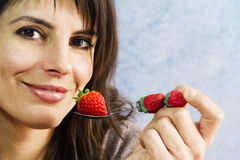 Smiling woman ready to eat strawberry Stock Images