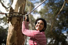 Woman ready to zip line in adventure park. Smiling woman ready to zip line in adventure park on a sunny day Royalty Free Stock Images