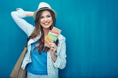 Smiling woman ready for travel with passport and ticket. Blue wall background Stock Photography