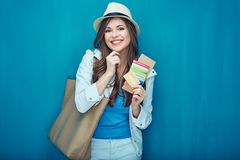 Smiling woman ready for travel with passport and ticket. Blue wall background Royalty Free Stock Photo