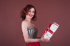 Smiling woman receives a gift. Studio shot Royalty Free Stock Images
