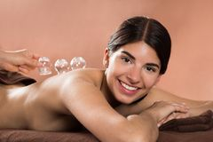 Smiling woman receiving cupping therapy Stock Image