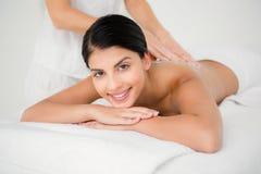 Smiling woman receiving a salt scrub massage Royalty Free Stock Photo