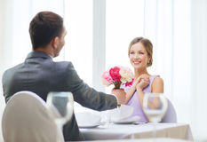 Smiling woman recieving bouquet of flowers Stock Photo