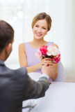 Smiling woman recieving bouquet of flowers Royalty Free Stock Images