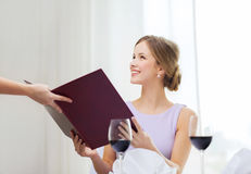 Smiling woman recieving menu from waiter Stock Photography