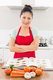 Smiling woman with recipe book and vegetables in kitchen Stock Photo