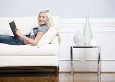 Smiling Woman Reclining on Couch With a Book. Cropped view of a woman relaxing on a white couch with a book and smiling at the camera. Horizontal format Royalty Free Stock Photos